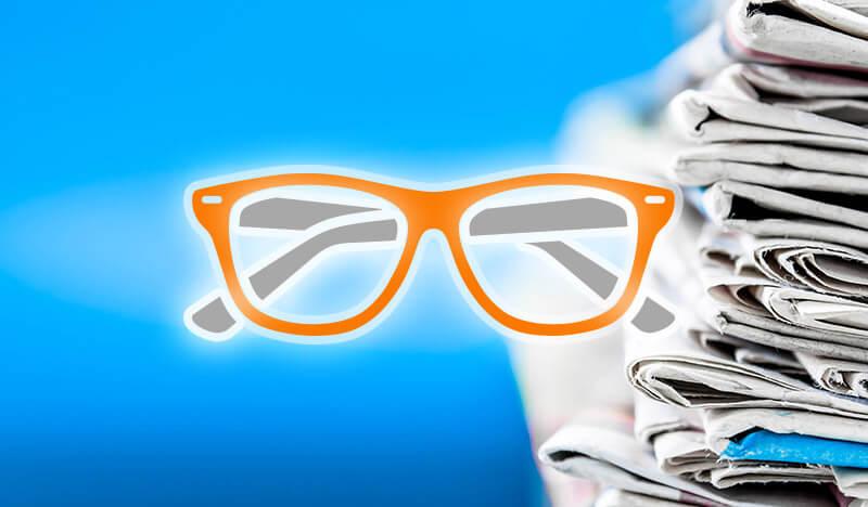 brille orange vor zeitungsstapel