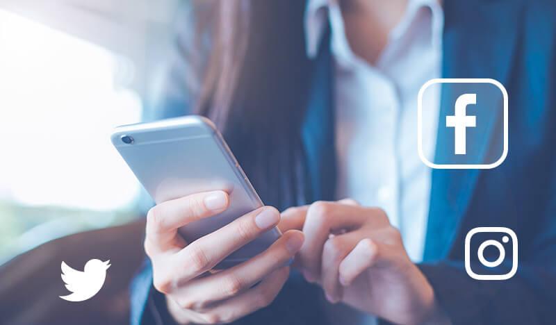 smartphone in hand social media logos