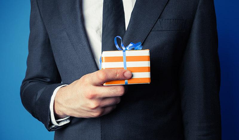 mann im anzug hält geschenk