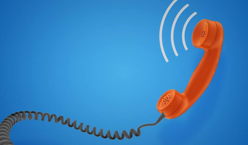 orangenes schnurtelefon vor blauem hintergrund